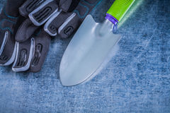 Metal hand spade safety gloves on metallic background agricultur Royalty Free Stock Image
