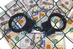 Metal handcuffs on the background of dollars under wire netting (lattice) Stock Photo