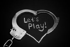 Lets play bdsm. Handcuffs for role-playing. Adult game concept. Handcuffs like heart with caption on black background. Metal handcuffs on dark background with Royalty Free Stock Photo