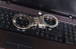 Metal handcuffs on laptop keyboard Stock Image