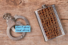 Metal handcuffs, paper message, hip flask. Royalty Free Stock Photos