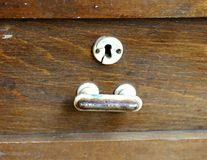 Metal handle and keyhole of an old wooden table. Royalty Free Stock Image