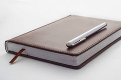 metal handle lying on a leather-bound brown diary which belongs Stock Photos