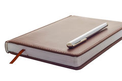 Metal handle lying on a leather-bound brown diary which belongs to businessman. Bookmark between the pages of the diary. Stock Photography