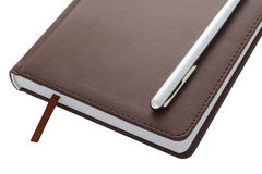Metal handle lying on a leather-bound brown diary which belongs to businessman. Bookmark between the pages of the diary. Royalty Free Stock Image