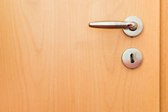 Metal handle on wooden door Royalty Free Stock Photos