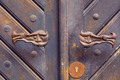Metal handles of wooden door with small faces Stock Photo