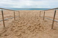 Metal handrail on beach. Shiny metal handrail at beach on background of sand and sea royalty free stock photography