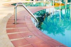 Metal handrail besides swimming pool. Silver metal handrail besides swimming pool stock image