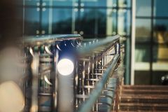 Metal handrails outdoor the modern building. Metal clean glossy handrails of the passage of the modern glass building outdoors. construction illuminated by royalty free stock photo