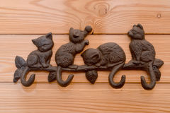 Metal hanger with hooks in the form of kittens on a wooden wall Royalty Free Stock Photography