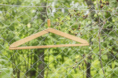 Metal hangers hanging on a metal fence on a background of greens Stock Photos