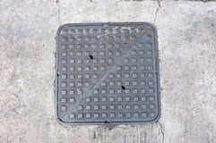 Metal hatch sewer manhole on pavement Stock Image