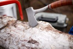 Metal hatchet or axe above a tree trunk. Metal hatchet or axe being held above a tree trunk with a hacksaw in the background during chopping of wood for fuel on Stock Image