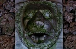 Metal head of a lion on a stone wall from which water once flowed royalty free stock image