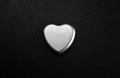 Metal heart. Decoration on black leather stock photos