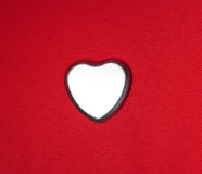 Metal heart. Shiny metal heart against red background Stock Images