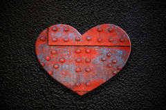 Metal heart on a dark texture Royalty Free Stock Photos