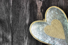 Metal heart on dark wood Stock Images