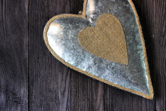 Metal heart on dark wood Stock Photography