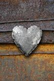 Metal heart on rusty background. Photo of metal heart on a rusting iron background stock photo