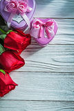 Metal heart-shaped present boxes red roses on wooden board celeb Royalty Free Stock Photo