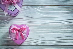 Metal heart-shaped small present boxes on wooden board celebrati Stock Images