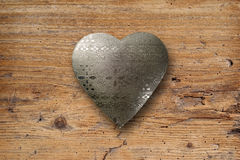 Metal heart on wood. Photo of an ornate metal heart on top of an old plank of wood stock photo