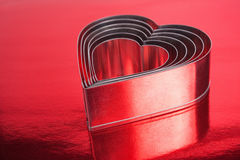 Metal hearts shaped. Some of the metal hearts shaped over red background.Shallow DOF Royalty Free Stock Image