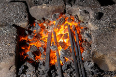 Metal is heated in the forge on coals Stock Photo
