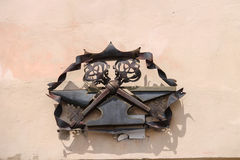 Metal heraldic sign with two crossed keys on a building wall Stock Photos