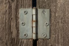Metal hinge on brown wooden planks with many screws in it. royalty free stock photography