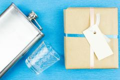 Metal hip flask, shot glass and gift box. On blue background. A gift for a man on holiday royalty free stock images
