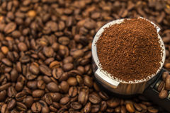 Metal holder with ground coffee on coffee beans Royalty Free Stock Photos