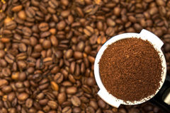 Metal holder with ground coffee on coffee beans. Professional metal holder with freshly ground coffee on coffee beans background. Close-up Royalty Free Stock Images