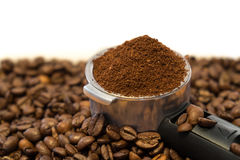Metal holder with ground coffee on coffee beans Stock Photography
