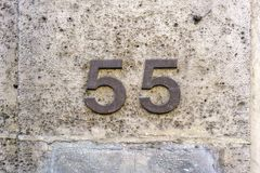 House number 55. Metal house  number fifty five 55 on a wall of natural stone Royalty Free Stock Images