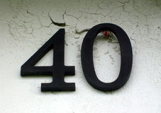 Metal house numerical marking 40. Metal house numerical marking 40 on a cracked wall stock image
