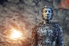 Metal human statue covered with letters. Against dramatic sky stock photo
