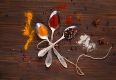 Metal i cucchiai e gli ingredienti su un fondo di legno Fondo con le spezie Immagine Stock