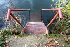 Metal i punti con il corrimano che conduce nel fiume calmo Fotografia Stock