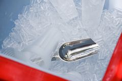 Metal ice scoop and plastic cup on the ice in bucket.  royalty free stock photos