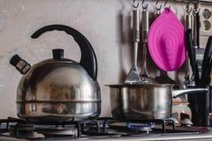 Metal il bollitore ed il vaso su una stufa di gas bruciante immagini stock