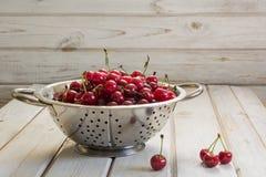 Metal il filtro con le bacche e la ciliegia mature su fondo di legno La colapasta ha riempito di ciliege sopra un bordo rustico Immagine Stock