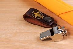 Metal il fischio con la sciarpa gialla dell'esploratore su fondo di legno Fotografia Stock