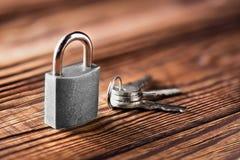 Metal il lucchetto con le chiavi argentate su vecchio fondo di legno Concetto di sicurezza e della proprietà con il simbolo di pr Fotografie Stock Libere da Diritti