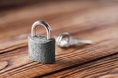 Metal il lucchetto con le chiavi argentate su vecchio fondo di legno Concetto di sicurezza e della proprietà con il simbolo di pr Fotografia Stock Libera da Diritti
