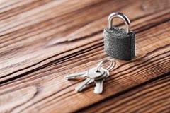 Metal il lucchetto con le chiavi argentate su vecchio fondo di legno Concetto di sicurezza e della proprietà con il simbolo di pr Immagine Stock