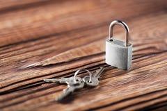 Metal il lucchetto con le chiavi argentate su vecchio fondo di legno Concetto di sicurezza e della proprietà con il simbolo di pr Immagine Stock Libera da Diritti