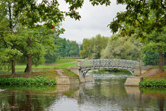 Metal il ponte sopra flusso nel parco del palazzo in Gatcina Immagini Stock Libere da Diritti